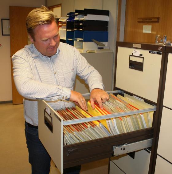 Utviklingsleiar Jarl Martin Møller blar i arkivet. Foto: Charlotte Hauge, Herøy kommune.