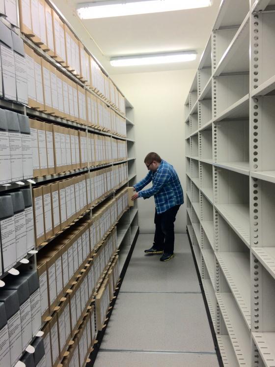 Arkivmedarbeidar Kristian Hove set avleveringa frå Averøy opp i hyllene. Foto: Guro Flø, IKAMR.