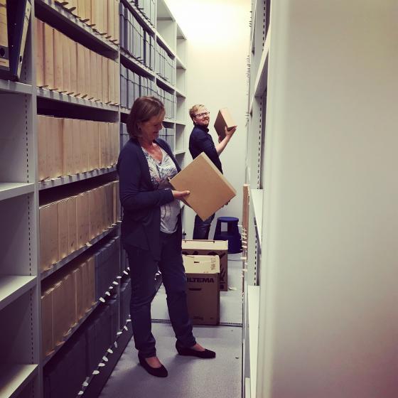 Konsulent Sølvi Knudsen og rådgjevar Dan Andre Fiskum Velle set opp arkiv i hyllene ved IKAMR. Foto: Åsta Vadset, IKAMR.